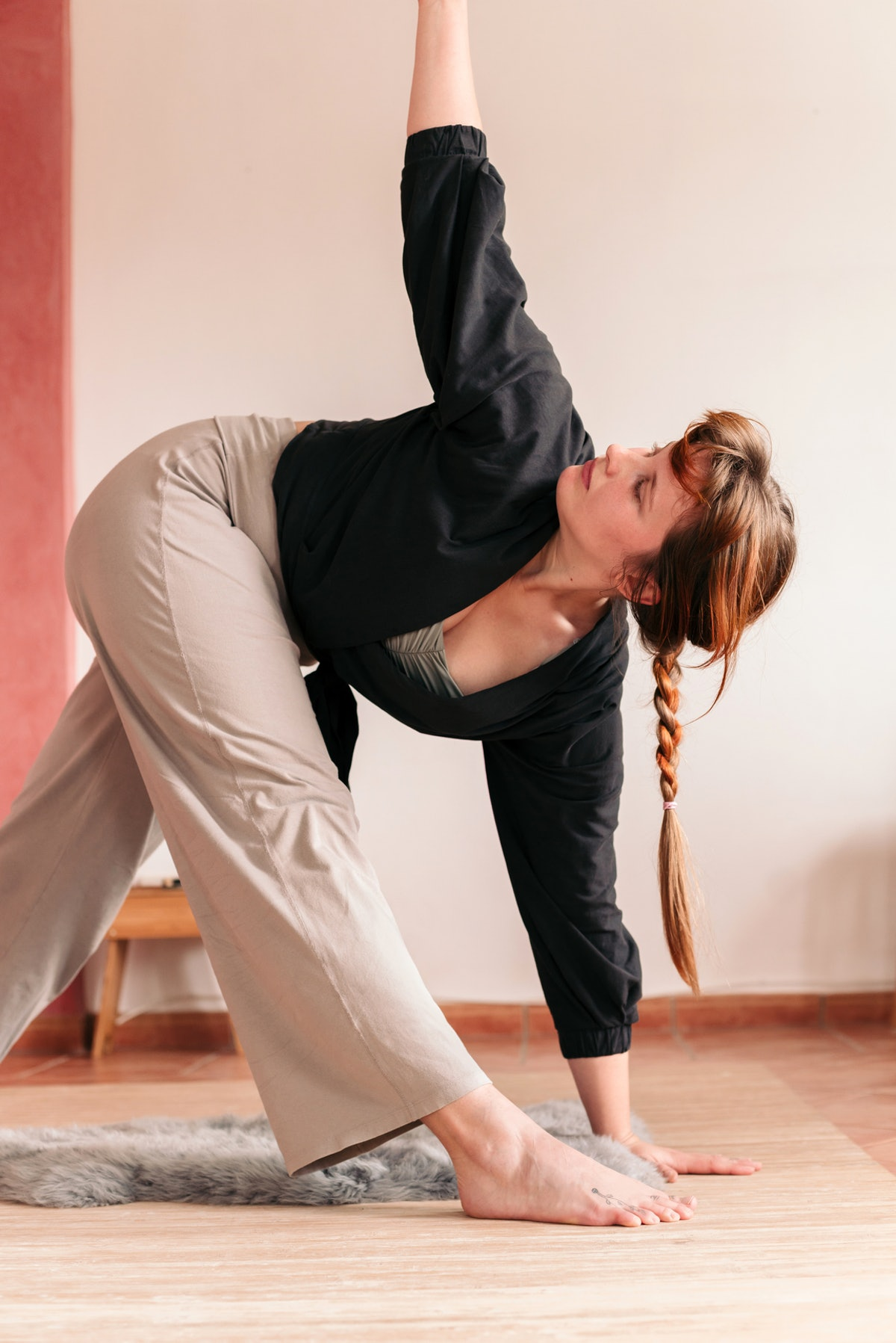 Young woman doing an easy yoga move in her dorm room.
