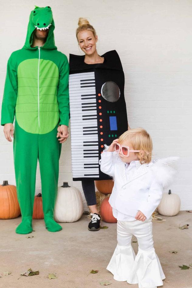Man dressed a crocodile, woman as a keyboard, baby as Elton John