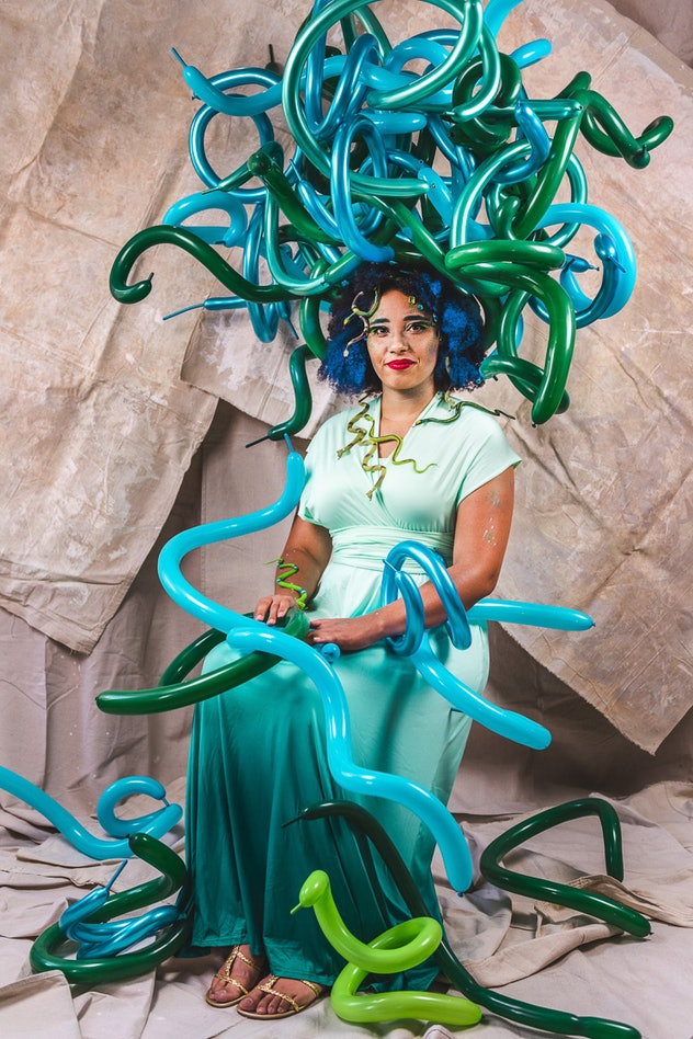 Woman sitting in chair dressed as Medusa with long balloons as snakes