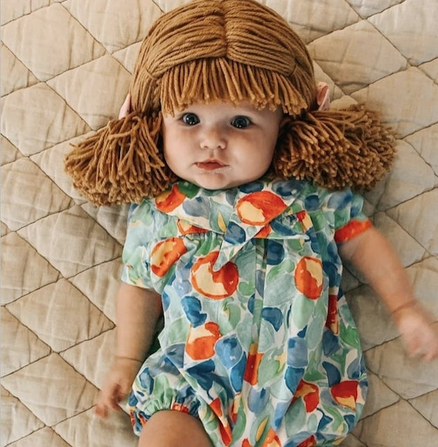 baby dressed as Cabbage Patch doll for Halloween, wearing romper and string wig