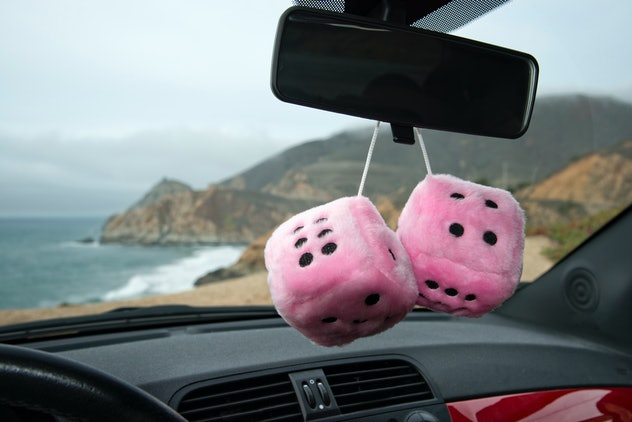 A pair of pink fuzzy dice hanging from rear view mirror