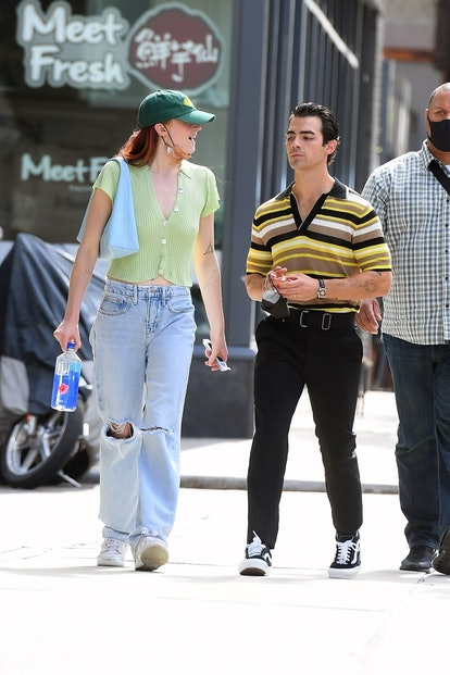 Sophie Turner wearing a green Jonas Brothers baseball hat, jeans, and a green top while carrying a b...