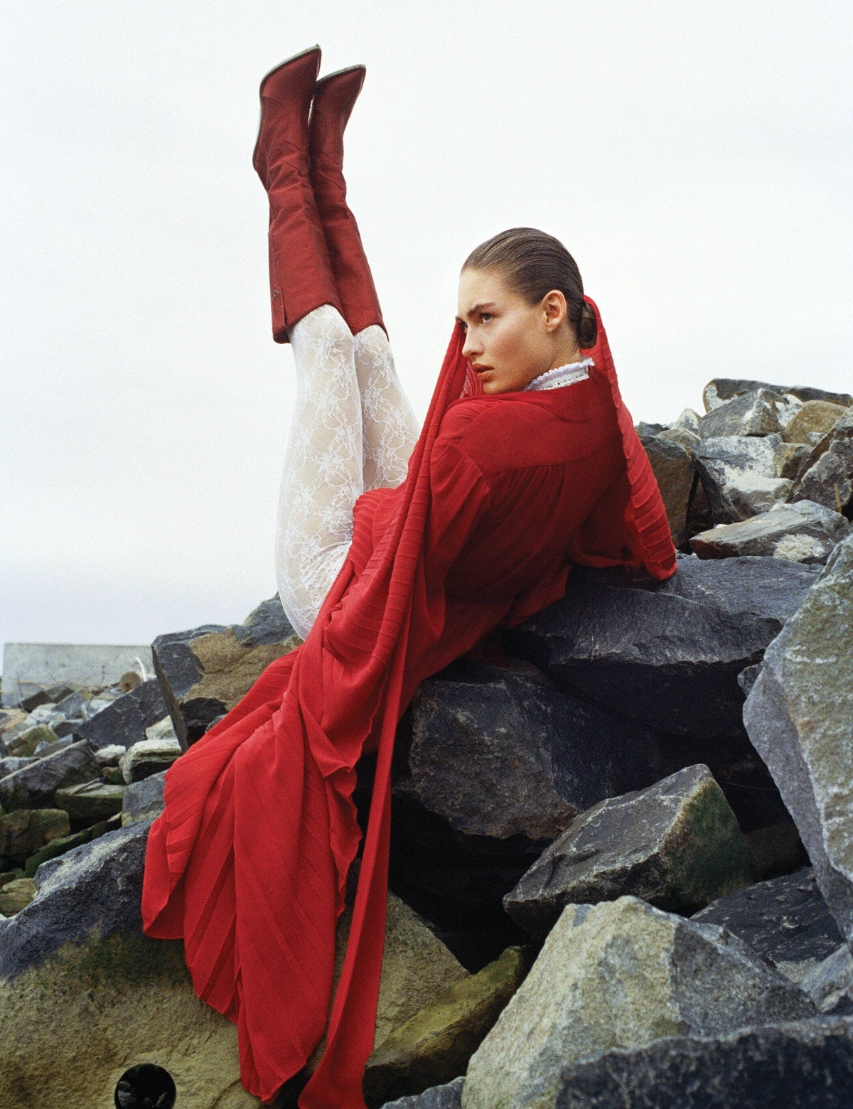 a woman in a red dress and tall brown boots reclines on a rocky outcropping