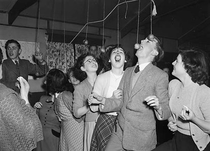 A group of party-goers bob for apples suspended from the ceiling.