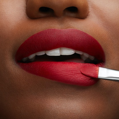 Woman applying MAC Cosmetic's Retro Matte Lipstick from its new Ruby's Crew collection.
