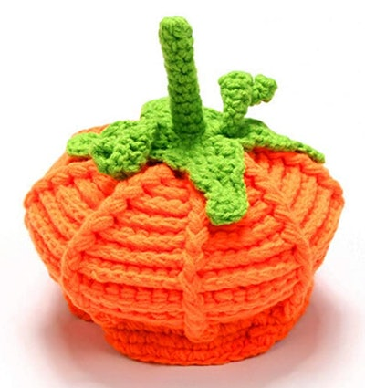"""Image of an orange baby wool hat with green """"stem."""""""