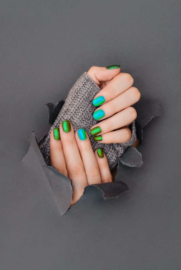 Manicured hand with green and blue polish