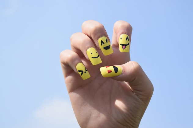 Close up of manicured hand; nail art looks like different emojis