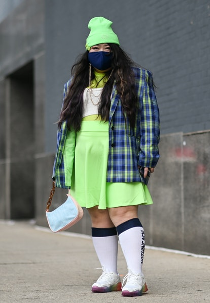 Scarlett Hao is seen wearing a bright green beanie, plaid jacket, green skirt and white sneakers out...