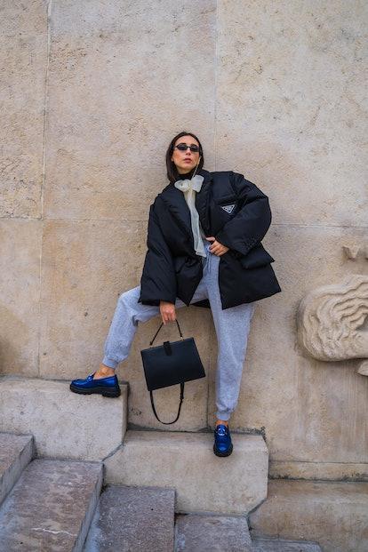 Gabriella Berdugo wears sunglasses from Ralph Lauren, a black puffed winter oversized jacket from Pr...