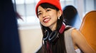 Young woman with headphones around her neck, happy that October 15, 2021 will be the best day of the...