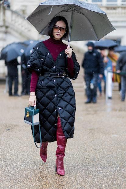 Yoyo Cao wearing a black puffy coat, turtleneck, overknees outside Stella McCartney on March 6, 2017...