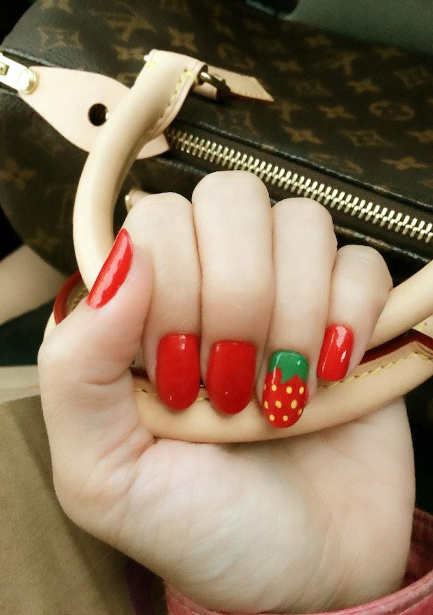 Manicured nails, strawberry design on ring finger