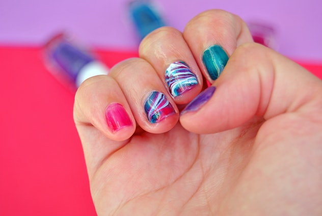 Up close photo of manicured nails with marble design