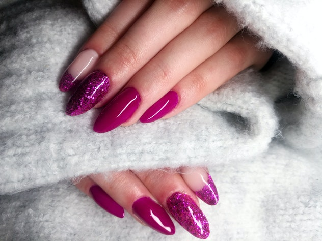 Closeup of manicure; magenta colors, solid and glitter shades