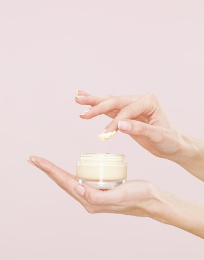 Woman's hand holding a jar of cream