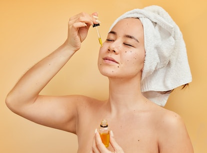 Woman applying serum to her face