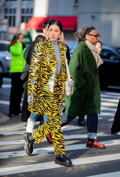 A guest is seen wearing yellow black jacket and pants with zebra print, turtleneck with graphic prin...