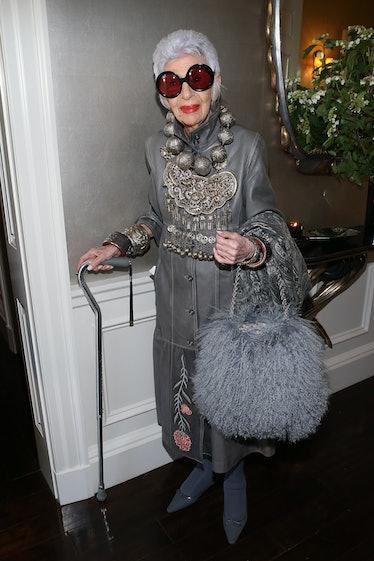 Iris Apfel wearing a grey leather coat