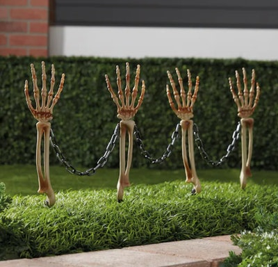Four skeleton hands/arms coming out of the ground