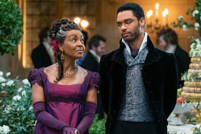 Lady Danbury in a deep purple gown sharing a knowing glance with the Duke of Hastings.