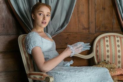 Daphne Bridgerton in a pale blue dress slipping a light blue glove onto her hand.