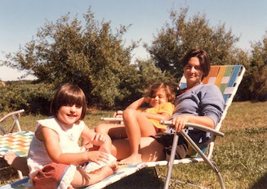 Young Ry, Cade, and Robin sitting in a lawn chair, relaxed and smiling