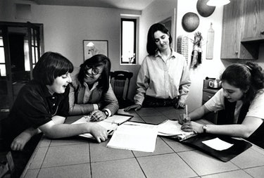 Ry, Sandy, Robin, and Cade around a table, doing what appears to be homework