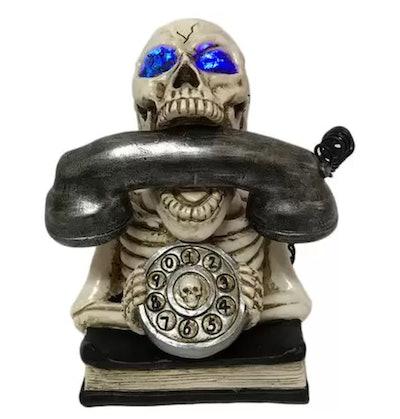 Halloween decor; skeleton holding phone, sitting on top of book