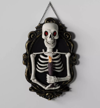 Skeleton holding a candle; wall decoration
