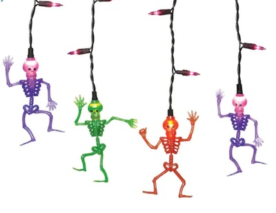 Four skeletons dangling from colorful icicle lights