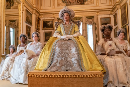 Queen Charlotte sitting in a throne in a decadent yellow dress with a large hoop skirt.