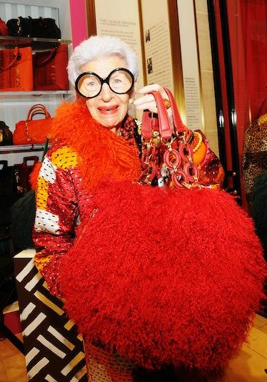 Iris Apfel holding up a giant puffball-shaped handbag