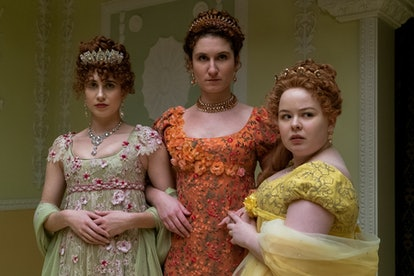 The Featherington Sisters standing in green, orange, and yellow gowns glancing at someone with a jud...