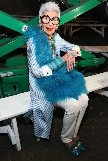 Iris Apfel wearing a blue feather boa