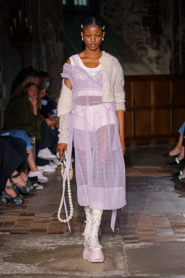 A model walks the runway for Simone Rocha during LFW wearing a sheer lilac dress, white undergarment...
