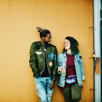 A young pair against a wall, forging a new relationship during the October 2021 new moon in Libra, w...