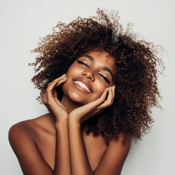 Woman touching skin and smiling