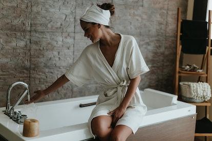 Woman preparing a bath in a robe
