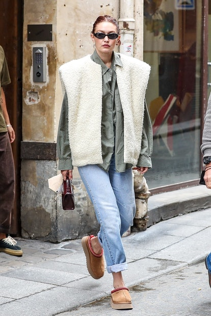 Gigi Hadid wears UGG Tazz slippers and a shearling vest while out and about in Paris on September 29...