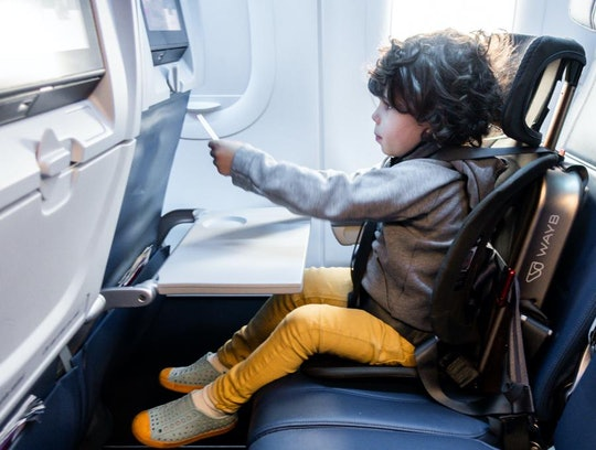Little kid sitting in Pico car seat installed on an airplane