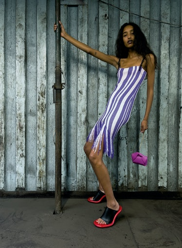 A model poses for JW Anderson's SS22 collection in a purple and white crochet dress.