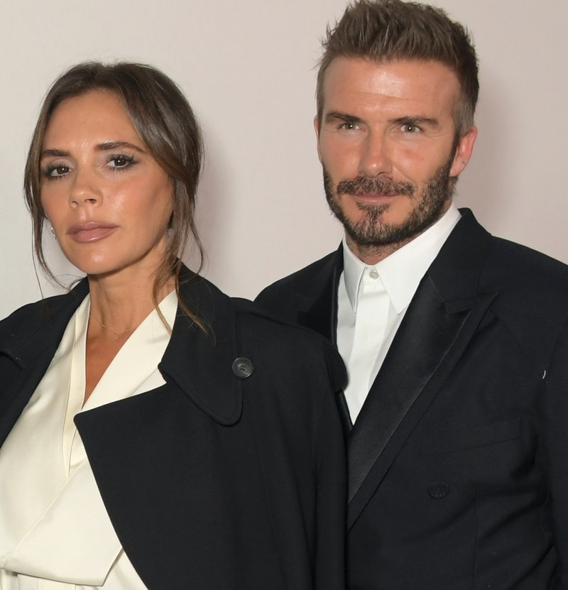 Victoria Beckham and David Beckham. They are dressed smartly both wearing black trench coats and whi...