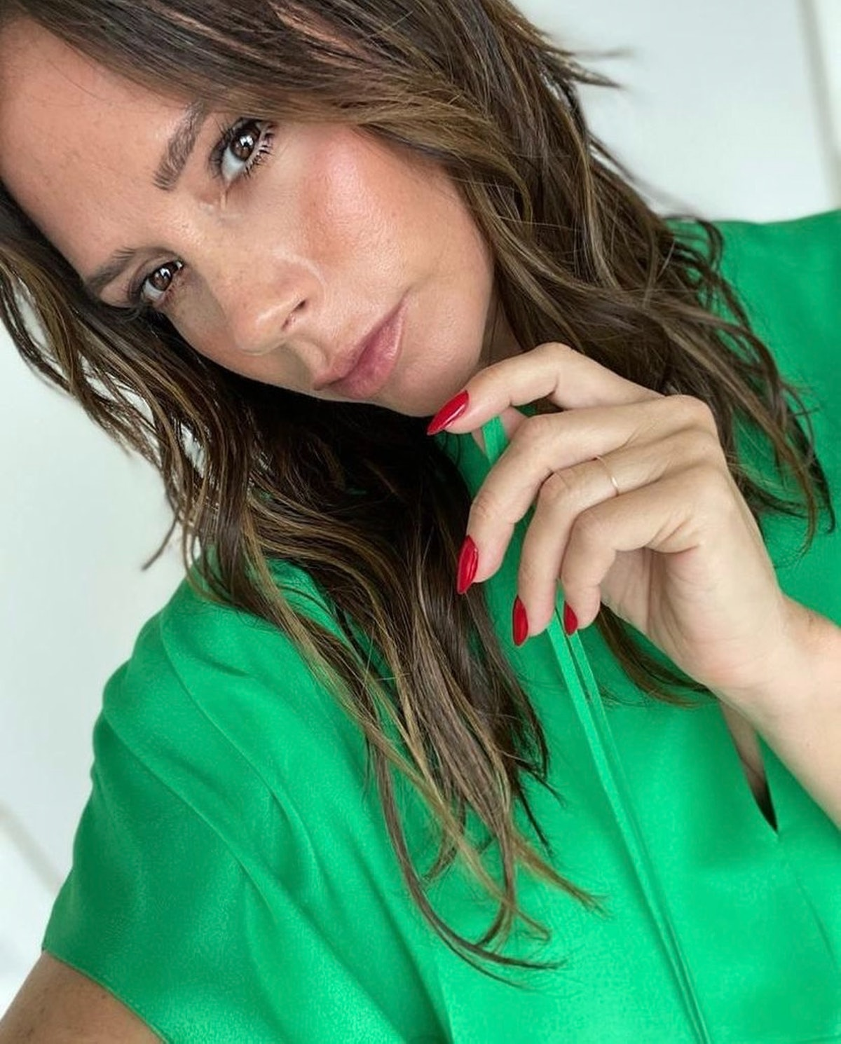 Victoria Beckham in a green blouse.