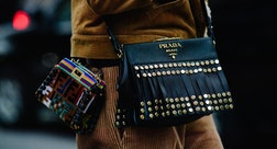 a woman with two designer purses slung over her shoulder
