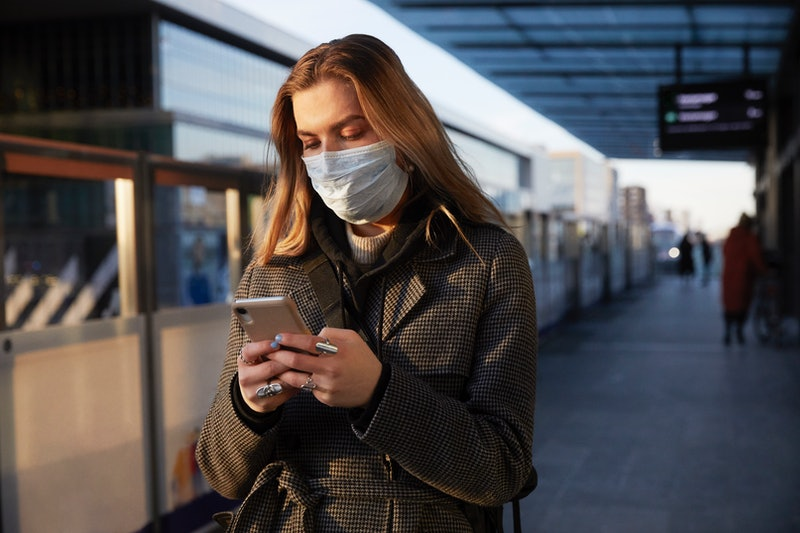 Woman in mask at train station looking at her phone.