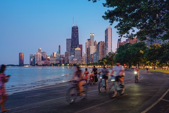 People riding bikes against the Chicago skyline