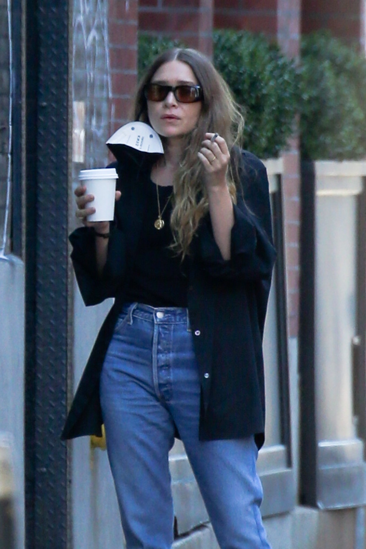 Ashley Olsen wears blue cuff jeans while grabbing coffee in NYC in 2021.