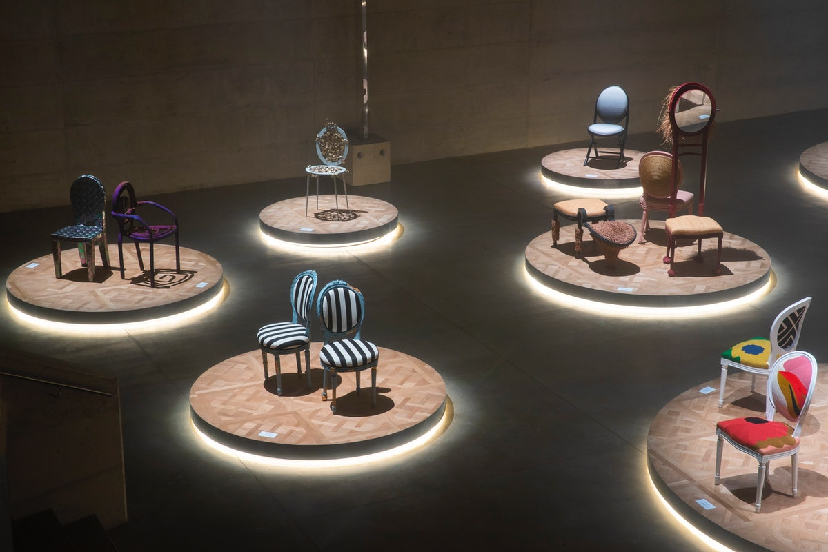 An array of chairs designed by artists in a dimly lit exhibition space