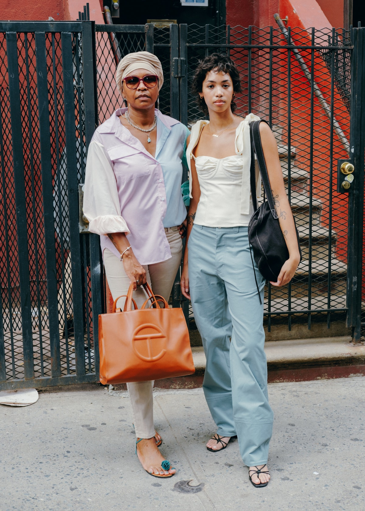 Two friends pose together.  One has a beige Telfar bag.